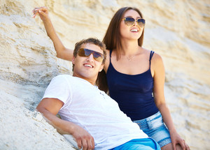 Young people in sunglasses leaning against sandy wall on the beach