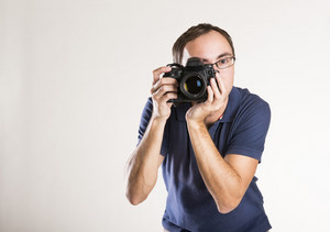 Young photographer with camera isolated on white background