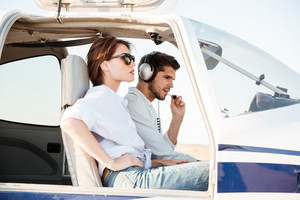 Young pilot and beautiful stewardess sitting together inside airplane cabin waiting for take off