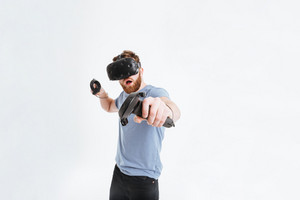 Young playful bearded man wearing virtual reality device standing over white background while holding joysticks in hands.