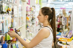 Young pregnant woman choosing baby stuff at baby shop store