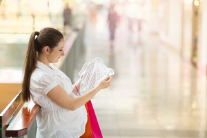 Young pregnant woman looking at new baby clothes in shopping mall