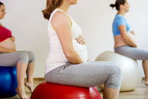Young pregnant women doing exercise using a fitness ball