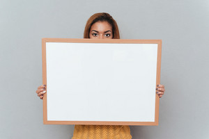 Young pretty african woman in yellow sweater hiding behind blank board. Isolated gray background