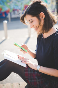 young pretty brown hair caucasian woman sitting on a small wall in town reading book while using a smartphone looking downward, smiling - culture, technology, social network concept