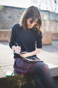 young pretty brown hair woman in town using writing down on a diary and using tablet, looking downward, smiling - multitasking, technology, working concept