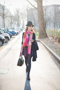 young pretty brown hair woman walking in town using smartphone, dressed with a colorful scarf, a checked skirt, a black sweater, sunglasses and hat - technology, social network, communication concept