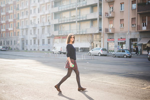 young pretty brown hair woman walking trough the streets using a smart phone, looking in camera, dressed with a checked skirt and a black sweater - relaxing, technology, social network concept