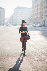 young pretty brown hair woman walking trough the streets using a smartphone, overlooking left, dressed with a checked skirt, a black sweater and a hat - relaxing, technology, social network concept