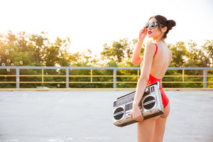 Young pretty brunette girl in sunglasses and red swimsuit holding old record player on the open road outdoors