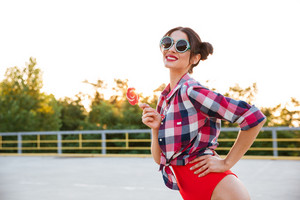 Young pretty brunette girl in sunglasses and red swimsuit posing and holding lollipop on the open road outdoors