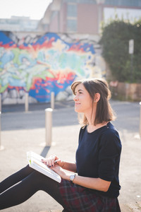 young pretty caucasian brown hair woman sitting on a small wall in town reading book  overlooking right - culture, relaxing concept