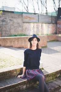 young pretty caucasian brown hair woman sitting on a staircase looking in camera, dressed with a checked skirt, a black sweater and a hat - relaxing, carefreeness concept