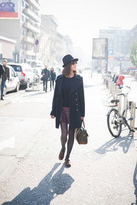 young pretty caucasian brown hair woman walking in the street of the city with a pair of sunglasses, a black coat and a hat, overlooking left, smiling - amusement, relaxing concept