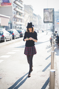 young pretty caucasian brown hair woman walking throug the streets of the city using a smartphone, looking downward the screen - technology, social network, communication concept