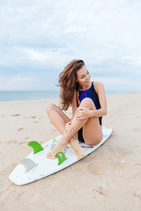 Young pretty girl relaxing on the beach sitting on her surf board