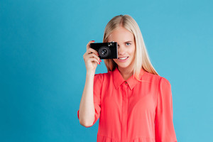 Young pretty girl taking photo using camera over blue background