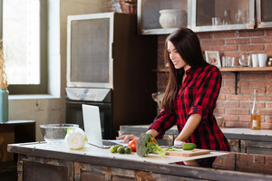 Young pretty Woman in red shirt standing at the table in kitchen with laptop and looking recipes. Side view