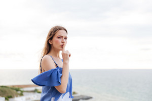 Young pretty woman making silent gesture with finger on lips over sea background
