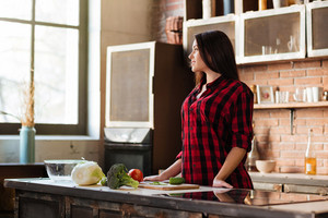 Young pretty Woman standing at the table in kitchen and looking away. Side view