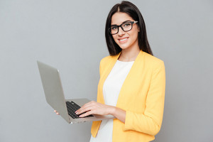 Young pretty woman wearing eyeglasses and dressed in yellow jacket using laptop over grey background.