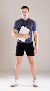 Young professional fitness coach standing in studio