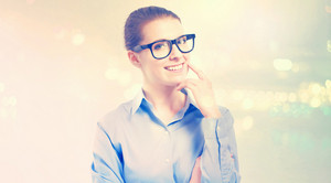 Young professional woman in glasses on abstract light background