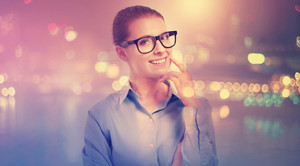 Young professional woman in glasses on blurred city background