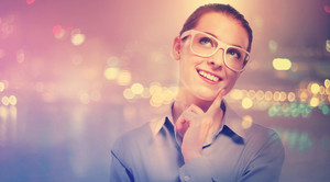 Young professional woman in glasses smiling and looking up on blurred city background