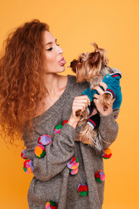Young red hair woman showing tongue to yorkshire terrier isolated on orange background