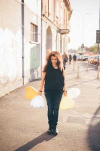 Young reddish brown hair caucasian woman playing in the street with baloon in shape of heart - youth, childhood, carefreeness concept - dressed with black shirt