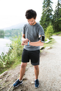Young runner at the lake in green nature with smart phone and smartwatch. Using a fitness app for tracking weight loss progress, running goal or summary of his run.