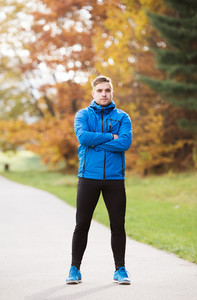 Young runner in blue jacket, arms crossed outside in colorful sunny autumn nature standing on an asphalt path leading through green grass. Trail runner training for cross country running.