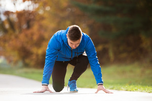 Young runner in blue jacket on an asphalt path leading through green grass in steady position. Trail runner training for cross country running outside in colorful sunny autumn nature.