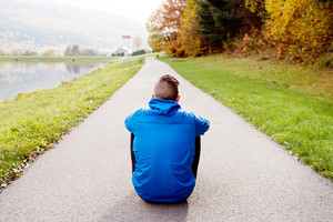 Young runner in blue jacket sitting on an asphalt path leading through green grass. Trail runner training for cross country running outside in colorful sunny autumn nature. Rear view.