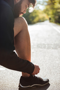 Young runner tying shoelaces in park. vertical photo