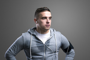 Young runner with headphones. Studio shot on gray background.