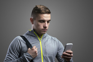 Young runner with smart phone. Studio shot on gray background.