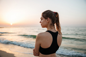 Young runner woman resting after jogging training on beach at sunset
