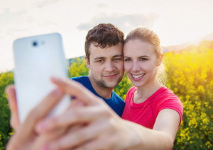 Young runners outside in spring canola field taking selfie with smart phone