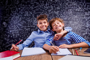 Young school boy and girl sitting at the desk, doing their homework against big blackboard with formulas and mathematical symbols