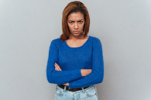 Young serious african woman in sweater and jeans with arms crossed looking at camera. Isolated gray background