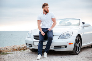 Young serious bearded man leaning on his car parked on beach