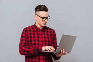 Young serious hipster in glasses and red shirt holding laptop in hands and writing something. Isolated gray background