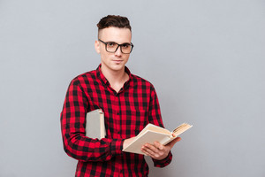 Young serious Man in glasses and shirt holding book in hands and looking at camera. Isolated gray background
