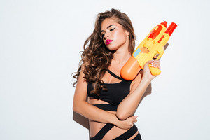 Young sexy girl holding water gun and posing in bikini isolated on the white background