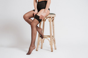 Young sexy woman in lingerie and stockings sitting on a chair isolated on a white background