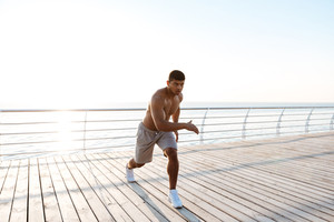 Young shirtless afro american sportsman doing squats on the pier in the morning