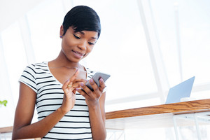 Young smiling african businesswoman texting on her smartphone in office