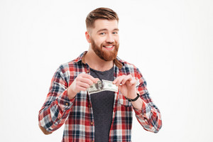 Young smiling bearded man tearing US dollars banknotes isolated on a white background